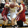 Monarch's Ashton Davis (middle) fights through Fairview's Katie Kuosman (left) and Julia D'Amico (right) during their basketball game at Monarch High School in Louisville, Colorado February 10, 2012. CAMERA/MARK LEFFINGWELL