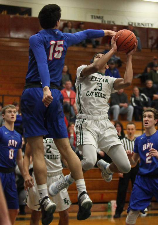 . Elyria Catholic\'s Jarred Logan hangs and gets a shot past RJ Sunahara of Bay during the first quarter. Randy Meyers -- The Morning Journal