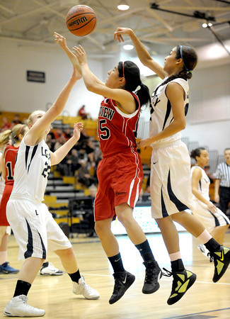 Fairview's Betty Yi (center) shoots between Legacy's Caitlyn Smith (left) and Kailey Edwards (right) during their basketball game at Legacy High School in Broomfield, Colorado February 13, 2012. CAMERA/MARK LEFFINGWELL
