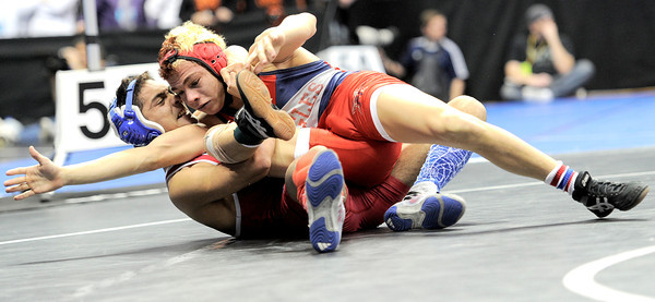Centaurus' Andre Aragon (left) flips Heritage's Kris Thomsen (right) over during the first round of the 2012 State Wrestling Tournament in Denver, Colorado February 17, 2012. CAMERA/MARK LEFFINGWELL
