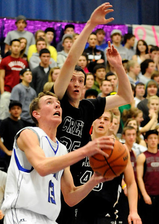 Longmont's Cade Kloster (left) tries to shoot while being pressured by Silver Creek's Brandon Bane (right) during their basketball game at Longmont High School in Longmont, Colorado February 17, 2011.  CAMERA/Mark Leffingwell
