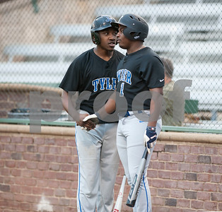 John Tyler High School baseball players Kentrell Wooten and Kiante Ross greet each other before being up to bat in their game against Mount Pleasant at Mike Carter Field in Tyler on Monday Feb. 19, 2018.  (Sarah A. Miller/Tyler Morning Telegraph)