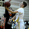 Monarch's Ben Beauchamp (right) slides a shot by Lakewood's Guy Young (left) during their basketball game at Monarch High School in Louisville, Colorado February 21, 2012. CAMERA/MARK LEFFINGWELL