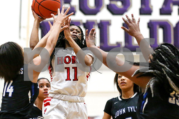 John Horn sophomore N'Yah Boyd (11) jumps to shoot the ball as John Tyler players attempt to block her shot during a 6A region 2 quarterfinal game at Eustace High School in Eustace, Texas, on Tuesday, Feb. 21, 2017. The John Tyler Lady Lions beat the Dr. John Horn Jaguars 65-50. (Chelsea Purgahn/Tyler Morning Telegraph)