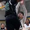 Doug Taylor Jr of Elyria Catholic shoots and scores over Evan Berrios of Clearview during the first quarter. Randy Meyers -- The Morning Journal