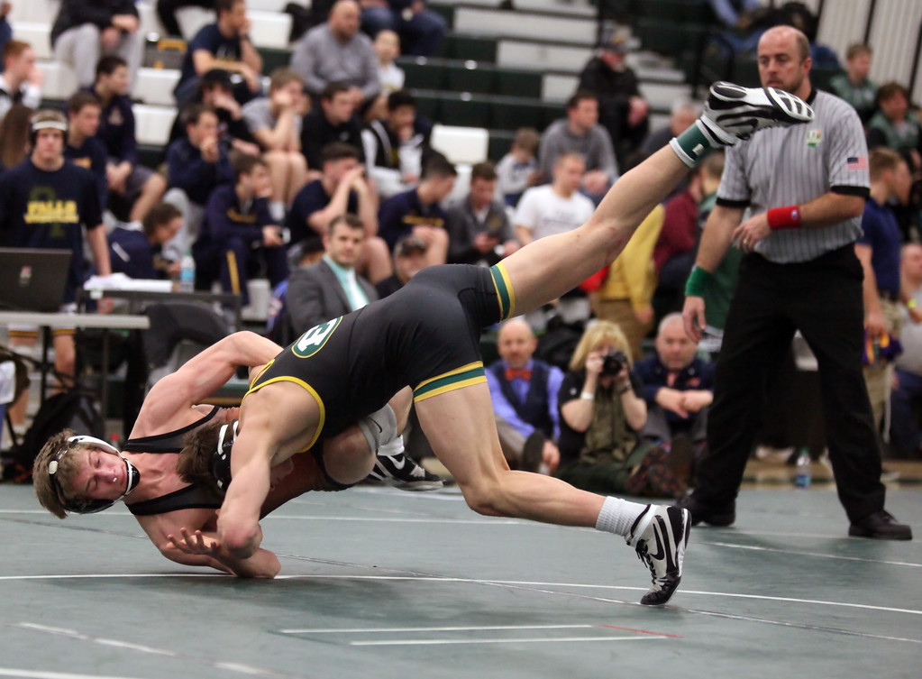 . Sam Dover of St. Edward drives Kevin Kelly of North Olmsted to the mat during the 138lb championship match. Randy Meyers -- The Morning Journal