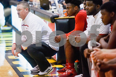 Carthage head coach Charlie Tucker squats as he watches the game during a high school basketball regional quarterfinal playoff game at Tyler Junior College in Tyler, Texas, on Tuesday, Feb. 27, 2018. The Carthage Bulldogs beat the Canton Eagles 57-42. (Chelsea Purgahn/Tyler Morning Telegraph)