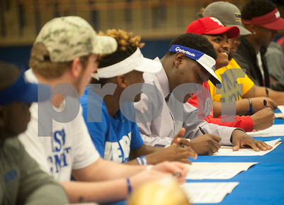 Adrian Harris, center, signs his letter of intent for Central Arkansas. Thirteen John Tyler High School seniors signed letters of intent to play collegiate football Wednesday Feb. 3, 2016 as part of National Signing Day.  (Sarah A. Miller/Tyler Morning Telegraph)