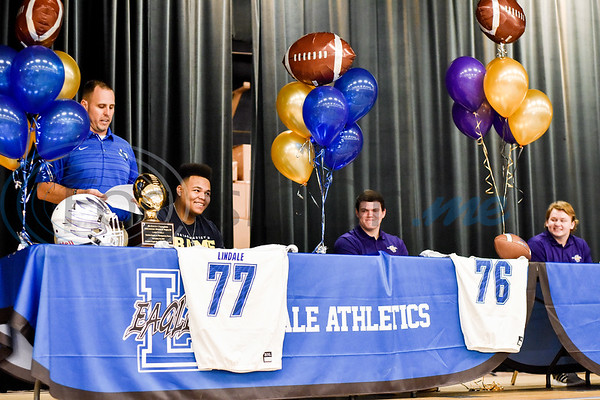 Lindale head football coach Chris Cochran speaks as Casen Chaney, James Sandifer and Dillon Heinaman sit on stage, smile and listen during a National Signing Day event at Lindale High School in Lindale, Texas, on Wednesday, Feb. 6, 2019. (Chelsea Purgahn/Tyler Morning Telegraph)