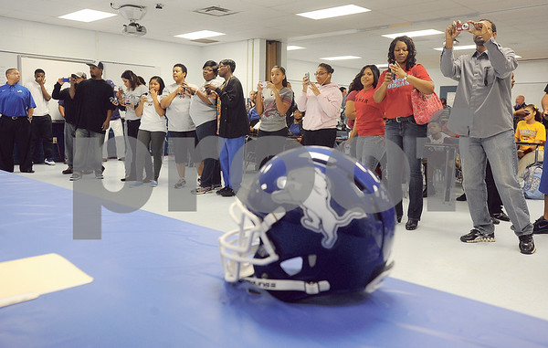 photo by Sarah A. Miller/Tyler Morning Telegraph  Family members of John Tyler High School senior football players who are committing to play football at the collegiate level take photographs of their loved ones Wednesday during a signing ceremony.