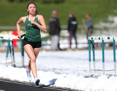 Medina's Jessica Wolf runs her leg of the 4x1600 race at the Medina Relays Saturday morning. Aaron Josefczyk/Gazette photo