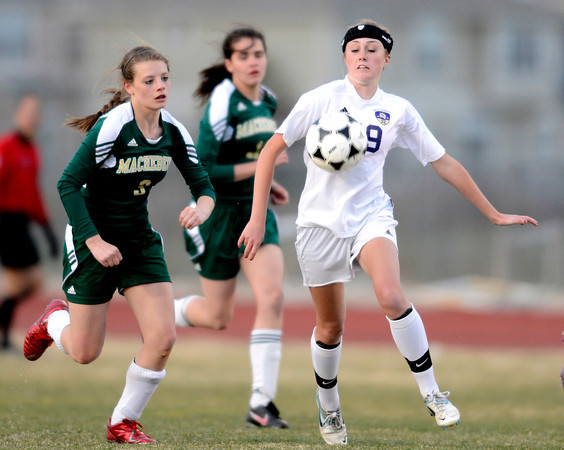 Holy Family's Daryl Mitzel (right) gains control of the ball while being pressured by Machenbuef's Rosie Sabin (left) during their soccer game at Holy Family High  in Broomfield, Colorado March 27, 2012. CAMERA/MARK LEFFINGWELL