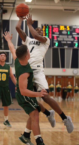 Octavius Wilson of Lorain shoots and scores over Johnny Matakovich of Amherst during the first quarter. Randy Meyers -- The Morning Journal