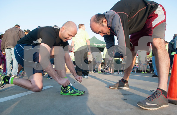 Waythan Foremar of Tyler ties his shoes and Kyle Carter of Tyler stretches before the start of the Fresh 15 15k race Saturday March 5, 2016 in Tyler.   (Sarah A. Miller/Tyler Morning Telegraph)