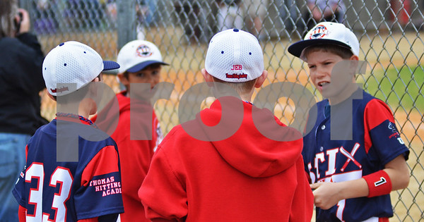 Players of Longview's Thomas Hitting Academy Stix chat and wait for their game on Saturday afternoon at the Strike Out Cancer for Make-A-Wish Foundation tournament at Faulkner Park. (Victor Texcucano)