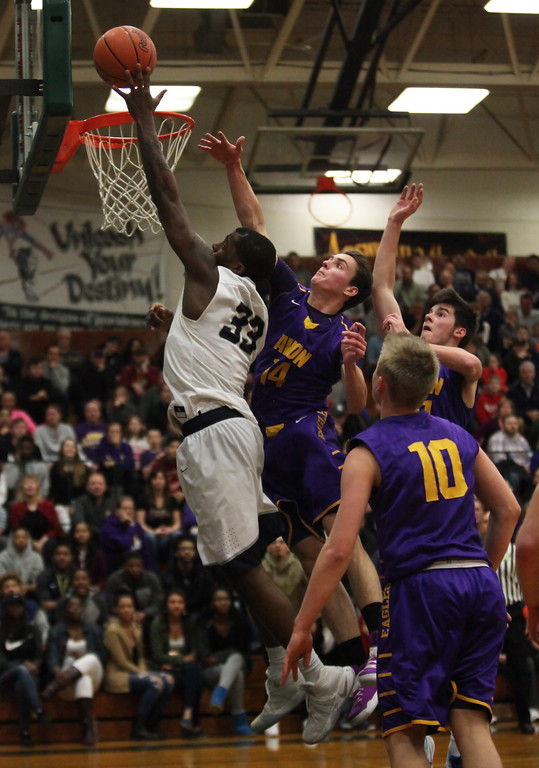 . Lorain\'s Naz Bohannon drives past Ryan Bertrand and Jake Parker of Avon for a lay up at the rim during the first quarte. Randy Meyers -- The Morning Journal