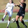 Legacy's Keira Bell (left) kicks the ball away from Monarch's Gina Ogg (right) during their soccer game in Westminster, Colorado April 10, 2012. CAMERA/MARK LEFFINGWELL