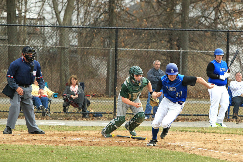 Leominster's Neil O'Connor sprints to first base in front of Nashoba catcher Nick Kane after a dropped third strike during Friday's game in Leominster. 	SENTINEL & ENTERPRISE / SCOTT LAPRADE