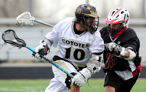 Monarch's Nathan Puldy (left) fights his way past Fairview's Sean LaVine (right) during their lacrosse game in Louisville, Colorado April 12, 2011.  CAMERA/Mark Leffingwell