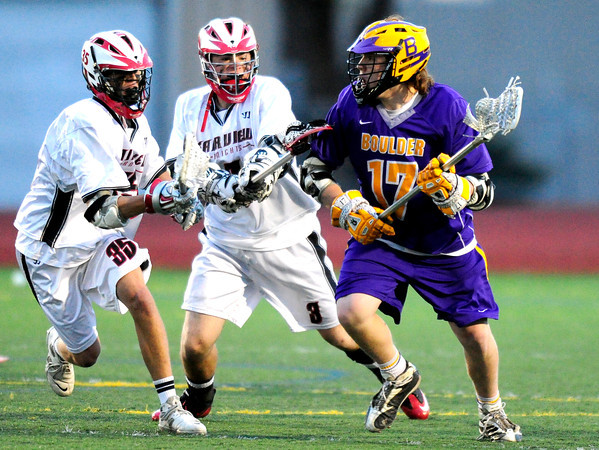 Fairview's Sean LaVine (left) and Luke Miller (middle) block Boulder's Ian Oden (right)  during their lacrosse game at Fairview in Boulder, Colorado April 12, 2012. CAMERA/MARK LEFFINGWELL