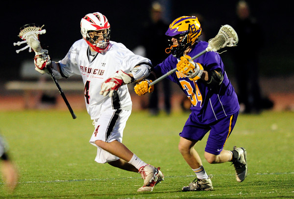 Boulder's Zach Brode (right) pressures Fairview's Jonny Combs (left) during their lacrosse game at Fairview in Boulder, Colorado April 12, 2012. CAMERA/MARK LEFFINGWELL