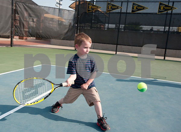 photo by Sarah A. Miller   Mason Connell, 4, learns to play tennis Tuesday during the first day of the new Tyler First Aces program at Tyler Junior College's JoAnn Medlock Murphy Tennis Center. The program pairs children with TJC and University of Texas at Tyler tennis team players so they can learn to play the game.