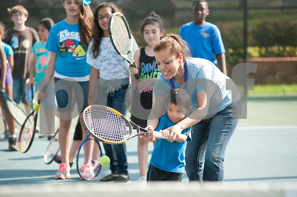 photo by Sarah A. Miller   Tuesday during the first day of the new Tyler First Aces program at Tyler Junior College's JoAnn Medlock Murphy Tennis Center. The program pairs children with TJC and University of Texas at Tyler tennis team players so they can learn to play the game.