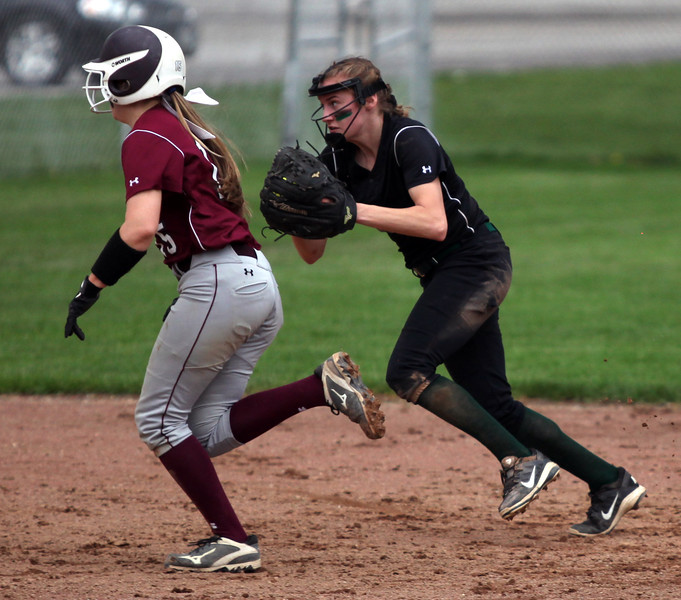 Elyria Catholic shortstop Sam Filiaggi fields a grounder and chases after baserunner Marissa Smiley of Rocky River. Randy Meyers -- The Morning Journal