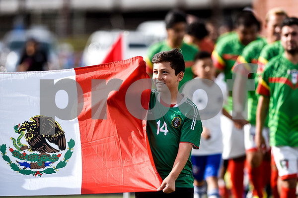 A young boy carries out a Mexican flag before a soccer game at Christus Trinity Mother Frances Rose Stadium in Tyler, Texas, on Sunday, April 2, 2017. Mexico beat Honduras 3-2. (Chelsea Purgahn/Tyler Morning Telegraph)