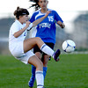 Holy Family's Taylor Johnson (left) kicks the ball away from Peak to Peak's Ivy Devries (right) during their soccer game at Holy Family in Broomfield, Colorado April 23, 2012. CAMERA/MARK LEFFINGWELL