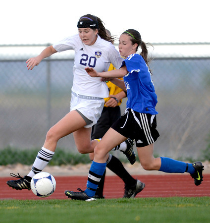 Holy Family's Abby Metzger (left) and Peak to Peak's Emily Gardener (right) race for the ball during their soccer game at Holy Family in Broomfield, Colorado April 23, 2012. CAMERA/MARK LEFFINGWELL