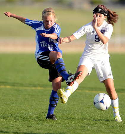 Peak to Peak's Brianna Wetmore (left) kicks the ball away from Holy Family's Domonique Giron (right) during their soccer game at Holy Family in Broomfield, Colorado April 23, 2012. CAMERA/MARK LEFFINGWELL