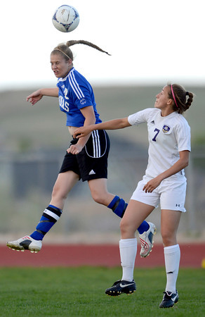 Peak to Peak's Belle Borel (left) heads the ball away from Holy Family's Ashley Burk (right) during their soccer game at Holy Family in Broomfield, Colorado April 23, 2012. CAMERA/MARK LEFFINGWELL