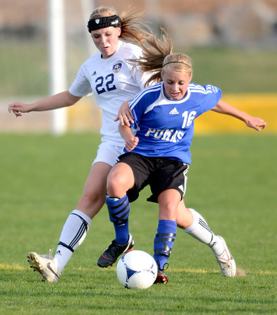 Peak to Peak's Brianna Wetmore (right) blocks Holy Family's Hannah Disberger (left) from the ball during their soccer game at Holy Family in Broomfield, Colorado April 23, 2012. CAMERA/MARK LEFFINGWELL
