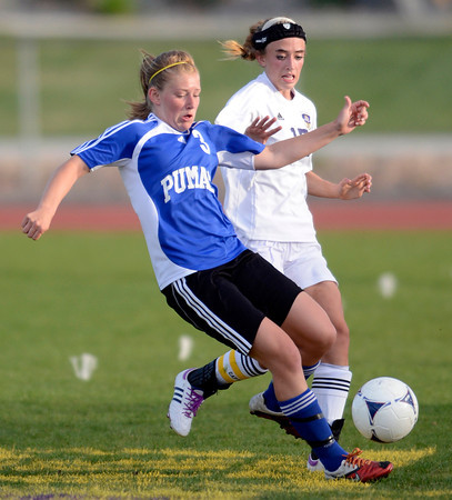 Peak to Peak's Lea Maxwell (left) races Holy Family's Monica Stokes (right) to the ball during their soccer game at Holy Family in Broomfield, Colorado April 23, 2012. CAMERA/MARK LEFFINGWELL