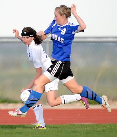Peak to Peak's Brynna Bostic (right) kicks the ball out of bounds while being pressured by Holy Family's Cassidy Hemp (left) during their soccer game at Holy Family in Broomfield, Colorado April 23, 2012. CAMERA/MARK LEFFINGWELL