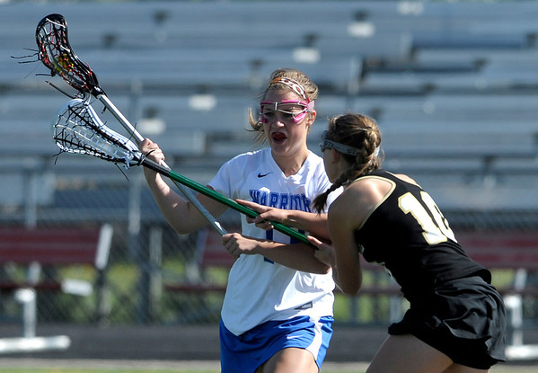 Centaurus' Carley Dvorak (left) is pressured byArapahoe's  Analise Stein (right) during their lacrosse game at Centaurus High School in Lafayette, Colorado April 27, 2012. BOULDER DAILY CAMERA/MARK LEFFINGWELL