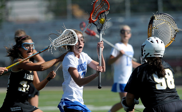 Centaurus' Olivia Holmes (middle) slips past Arapahoe's Margot Cohn (left) and Brooke Engel (right) for a goal during their lacrosse game at Centaurus High School in Lafayette, Colorado April 27, 2012. BOULDER DAILY CAMERA/MARK LEFFINGWELL