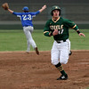 Kyle Dalzell of Amherst runs to third base as Chris Verda of Midview looks for a relay from the outfield. Randy Meyers -- The Morning Journal