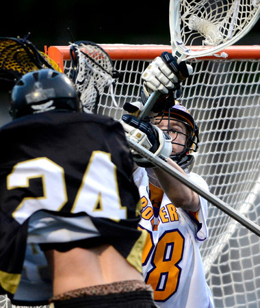 Boulder's Auston Billot (right) blocks a shot from Monarch's David Whitaker (left) during their lacrosse game at Recht Field in Boulder, Colorado April 5, 2012. CAMERA/MARK LEFFINGWELL