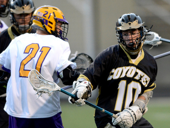 Monarch's Nathan Puldy (right) dodges around Boulder's Leete Skinner (left) during their lacrosse game at Recht Field in Boulder, Colorado April 5, 2012. CAMERA/MARK LEFFINGWELL