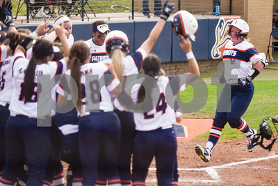 Teammates gather at home plate as UT Tyler's Lynsey Mitchell (21) runs to home plate after hitting a home run during a college softball game at the University of Texas at Tyler in Tyler, Texas, on Friday, April 6, 2018. UT Tyler beat East Texas Baptist University 4-2. (Chelsea Purgahn/Tyler Morning Telegraph)