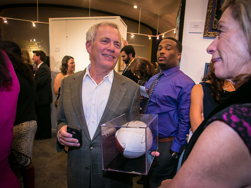 David Millstein holds a signed football he bought at the auction during the grand opening of the Vernon Davis Gallery in Santana Row in San Jose on Monday, December 10th, 2012.