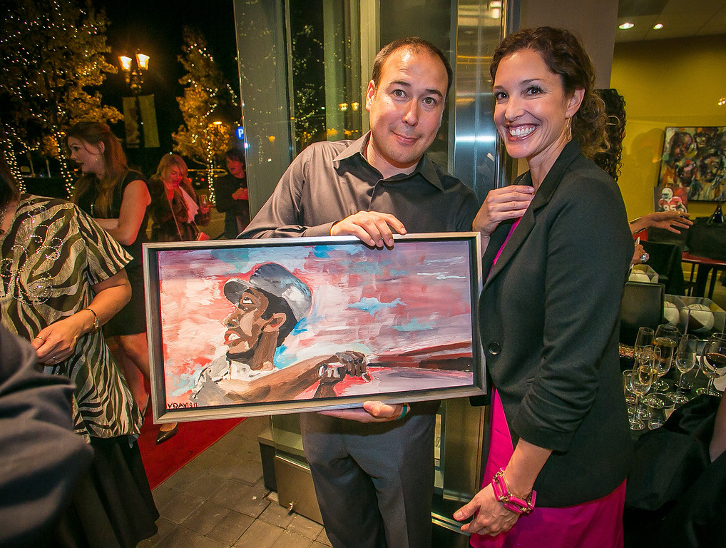 Paula and Doug Raetz with a the Vernon Davis painting of Hank Aaron at the grand opening of the Vernon Davis Gallery in Santana Row in San Jose on Monday, December 10th, 2012.