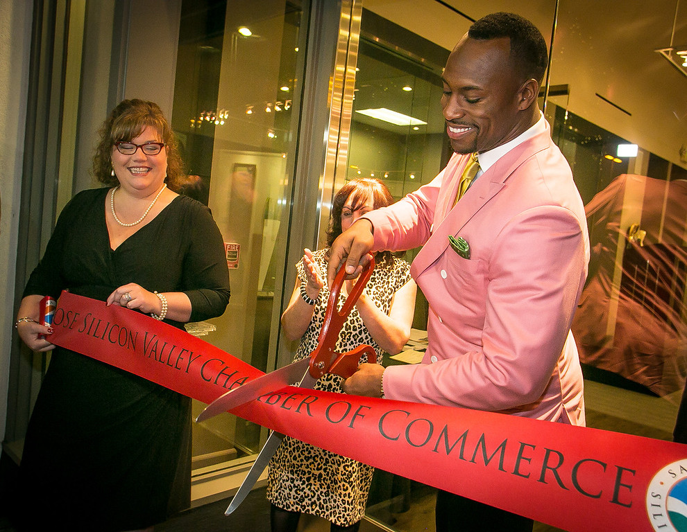 Stephanie Caldwell with the San Jose Chamber of Commerce, left, and Samina Masood, with the Vernon Davis Foundation for the Arts watch as Vernon Davis cuts the ribbon cutting during the grand opening of the Vernon Davis Gallery in Santana Row in San Jose on Monday, December 10th, 2012.