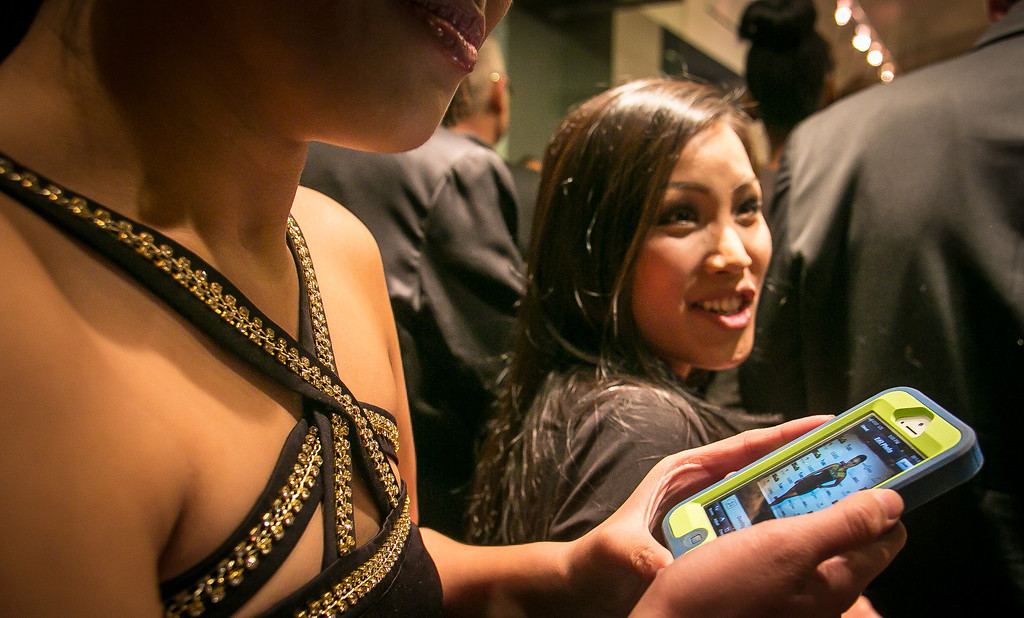 Steph Ng holds her phone with a picture of herself on the red carpet as Jenny Lau looks on during the grand opening of the Vernon Davis Gallery in Santana Row in San Jose on Monday, December 10th, 2012.