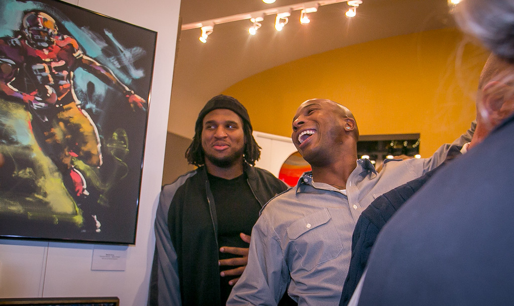 49ers Parys Haralson laughs after he bought a Vernon Davis painting of 49er Justin Smith during the grand opening of the Vernon Davis Gallery in Santana Row in San Jose on Monday, December 10th, 2012. In the background is 49ers defensive tackle Ray McDonald.