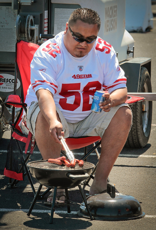 Edgar Monjarvas of Watsonville cooks hot dogs on the grill at Candlestick Park before the 49er-Texans game in San Francisco, Calif., on August 26th, 2011.