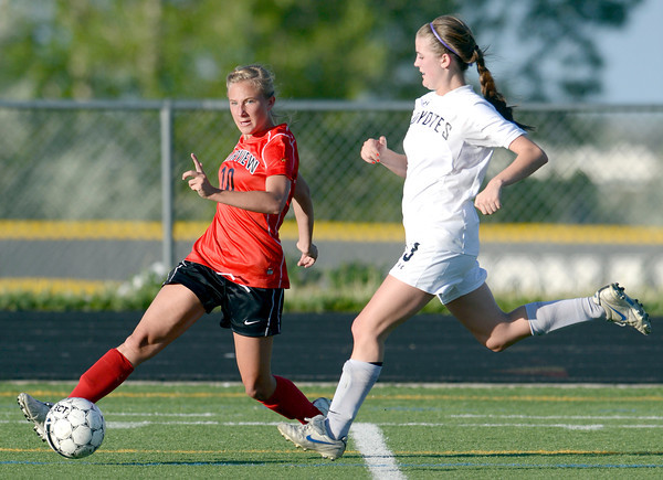 Fairview's Nikola Machalek (left) passes the ball past Monarch's Courtney Richard (right) during their soccer game in Louisville, Colorado May 1, 2012. CAMERA/MARK LEFFINGWELL