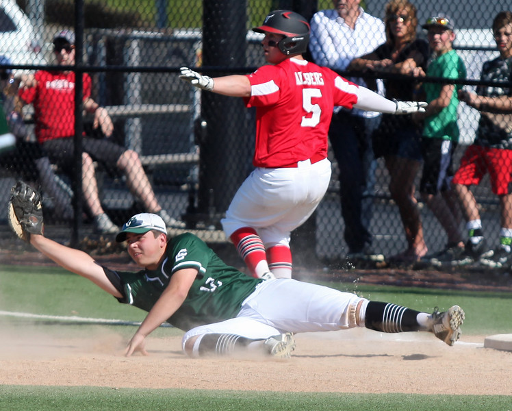 Randy Meyers -- The Morning Journal Elyria Catholic first baseman Michael Nedwick holds on for the out as Owen Albers of Lutheran West reacts to the call.